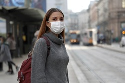 Student girl with protective mask waiting public transport in street. Young woman with surgical mask waiting tram at the stop in gray polluted city.