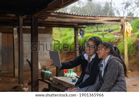 Student girls from the rural area take a selfie with their tablet.