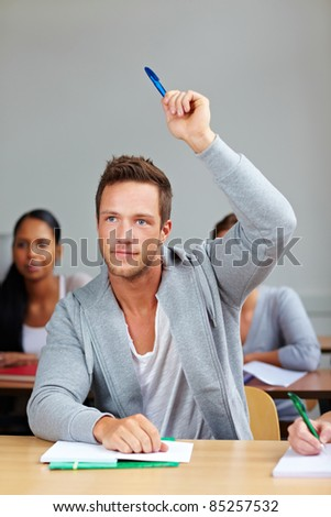Student giving answer in class with his hand raised