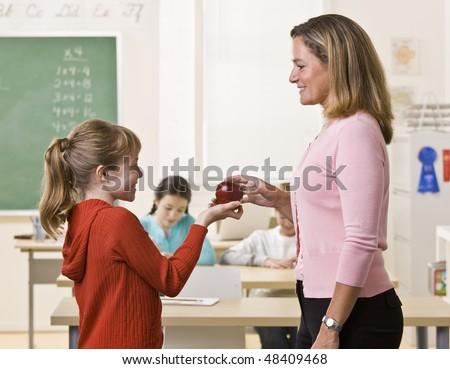 Student giving teacher apple
