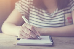Student hand holding pencil writing doing examination in university ,students in uniform attending exam classroom educational school: Young female business writes information from portable net-book