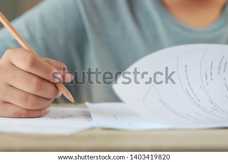 Student hand testing doing test exam with pencil drawing selected choices on answer sheet in school final exams at college or university. Taking multiple choice for assessment in examination classroom #1403419820