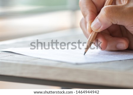 Student hand testing doing test exam with pencil drawing selected choices on answer sheet in school final exams at college or university. Taking multiple choice for assessment in examination classroom #1464944942