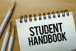 Student Handbook text written on a notebook with pencils