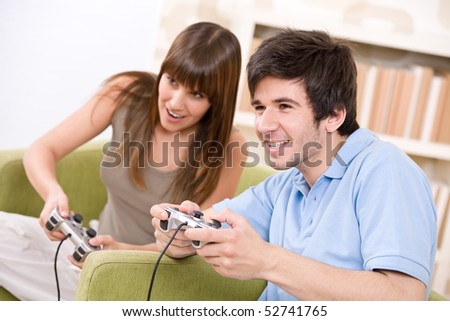 Student - happy teenagers playing video game with control pad in living room