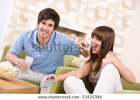 Student - happy teenagers watching television holding remote control