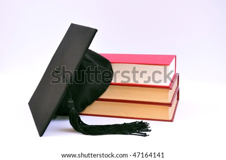 Student hat on books on white,