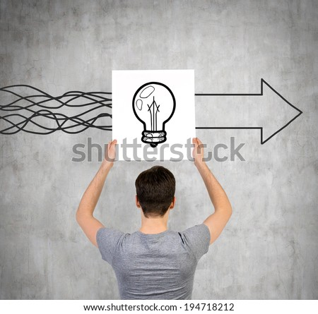 Student holding an \'light bulb\' poster, and a wall sketch of arrow.