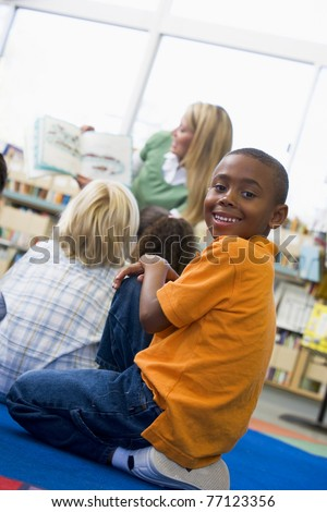 Student in class looking at camera with teacher reading in background (selective focus)