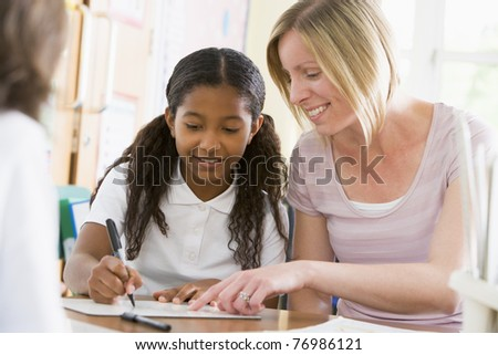 Student in class taking notes with teacher helping