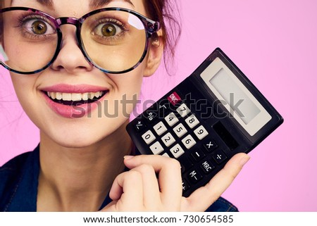 student in glasses cheerful in hand calculator on pink background portrait