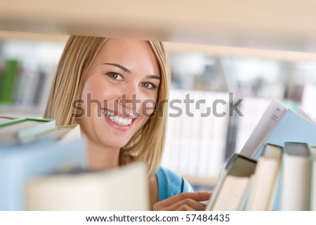 Student in library - cheerful woman look through bookshelf, hold book