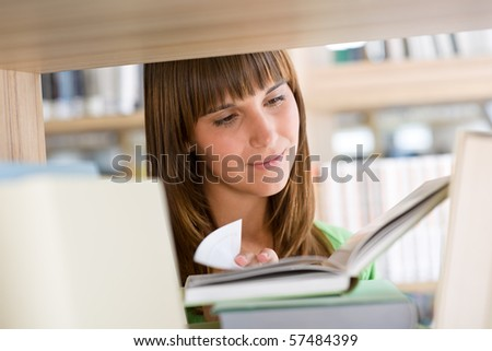 Student in library - happy woman read book stand at bookshelf