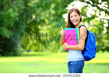 Student in park showing happy thumbs up success sign. Mixed race Asian Caucasian woman university student holding books outside. - stock photo