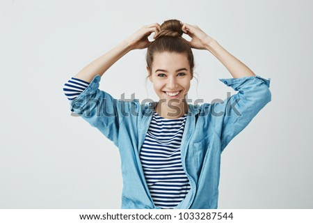 Student is ready to start working on her painting. Portrait of beautiful happy girl making bun hairstyle, pulling hair with hands and smiling broadly at camera. standing against gray background