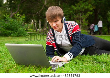 Student laying on grass and using laptop outside school
