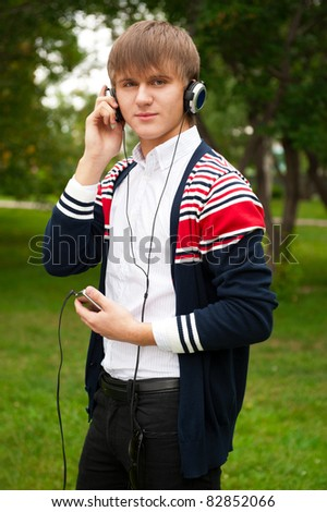 Student listening language course in headphones outside school