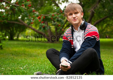 Student outside sitting on green grass and listening music via his player and headphones