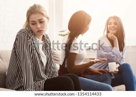 Student outsider. Upset girl sitting alone, ignored by classmates #1354114433