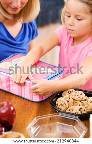 Student: Parent And Child Putting Together School Lunch