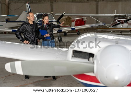 Student Pilot and Instructor Check an Aircraft for Safety in a Hangar. Flight instructor talking to female trainee pilot. They are standing next to small planes in hangar.