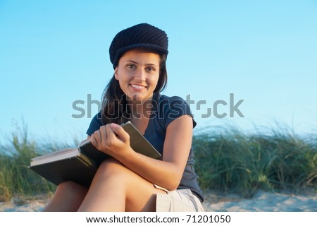 Student pretty young woman with book on the beach