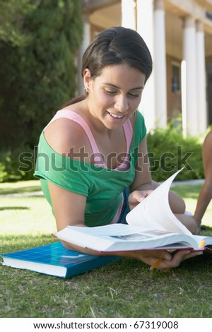 Student reading on the grass