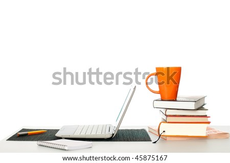 student's working and learning place with pile of books and laptop