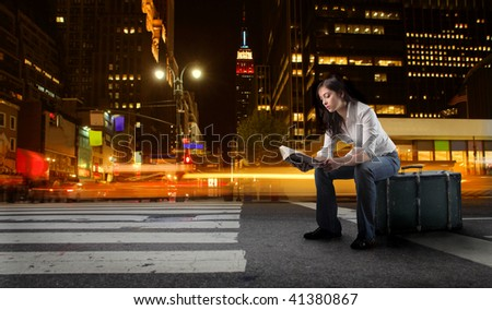 student seated on suitcase in a new york city street