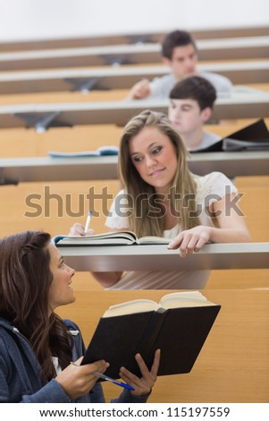 Student showing friend a book in the lecture hall