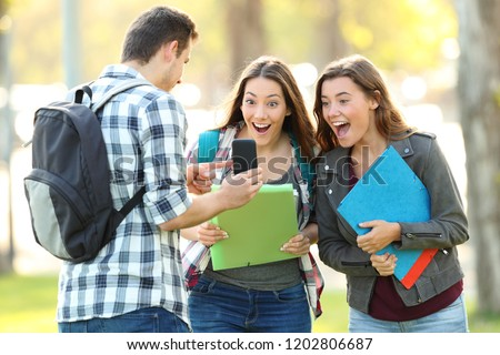 Student showing phone content to a friends outdoors in a park #1202806687
