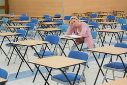 Student sitting and talking at desk in empty exam hall