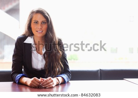 Student sitting at a table while looking at the camera