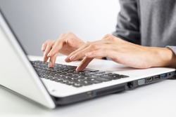 Student sitting at desk and working at laptop computer. Close-up of female hand typing at notebook computer. Journalist writing at workplace in office. Business innovation and digital technologies