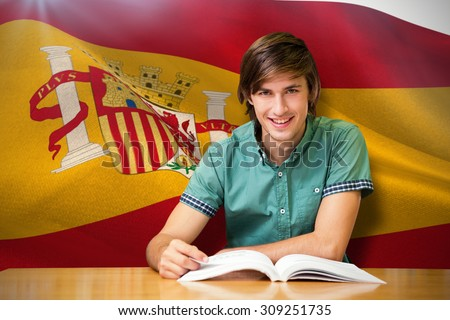 Student sitting in library reading against digitally generated spanish national flag