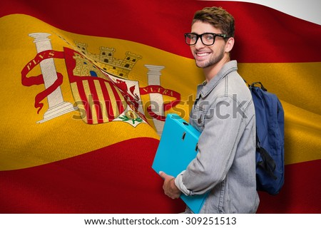 Student smiling at camera in library against digitally generated spanish national flag