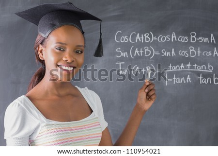Student smiling while showing the blackboard in a classroom