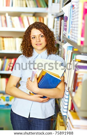 Student standing with books in the library and smiling