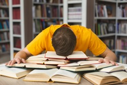 Student studying hard exam and sleeping on books in library, free space
