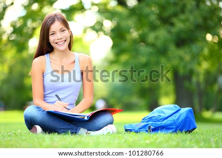 Student studying in park. Joyful happy asian girl student sitting writing and reading outside on university campus or park. Mixed race Chinese Asian / Caucasian female student woman looking at camera.