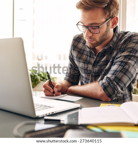 Student studying to become a businessman, while wearing glasses and a check shirt while sitting behind his notebook at his desk