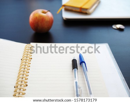 student supplies, notebooks and textbooks, pens and apple, student desk