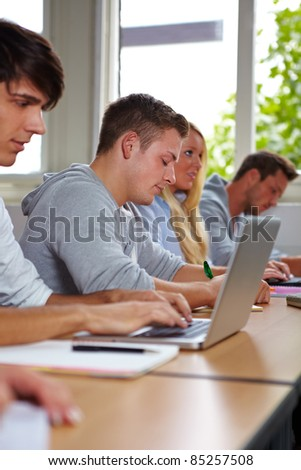 Student taking notes at laptop in university class