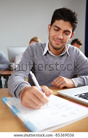 Student taking some notes in university class - stock photo