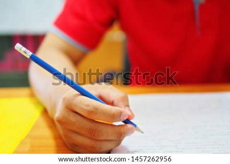 Student taking test with a pencil in the room of testing center at the college or university campus, selective focus picture of learner, education or academic concept, idea for professional studying