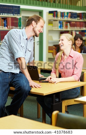 Student talking with a female student in library