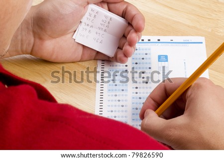 Student using a cheat sheet to cheat on his test.
