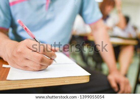 Student using a pen writing or taking notes during the lecture hours in high school, collage, or university campus; education concept picture of young learners participated in the training session