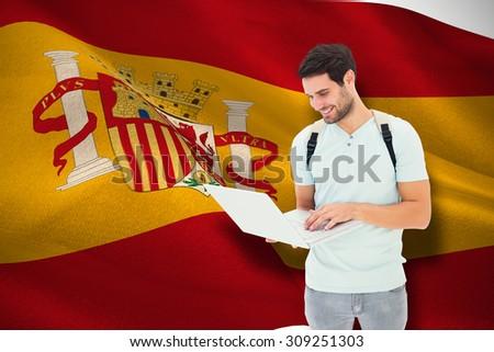 Student using laptop against digitally generated spanish national flag