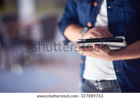 student using tablet computer for education in school, university interior in background stock photo